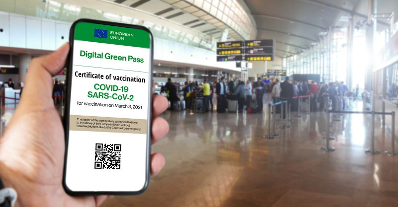 The digital green pass of the European union with the QR code on the screen of a mobile held by a hand with blurred airport in the background. Covid-19 Vaccine.